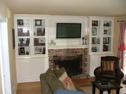 built in white entertainment center cabinets around fireplace with
