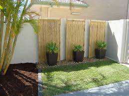 tall planters and rocks against wall lined by stones bamboo garden