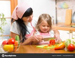 mother teaching child making salad in kitchen mom and kid