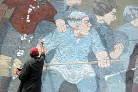 cambridge arts restores mural artist bernard lacasse applies a fresh coat of blue paint to one of the protesters