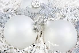three white ornaments nestled in white paper with