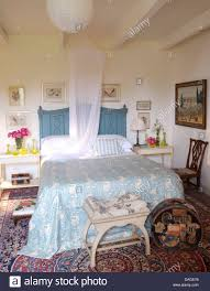 mosquito net above bed with painted blue headboard and blue white