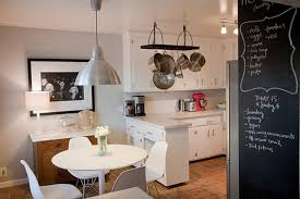 minimalist white kitchen with white dining table and white chairs