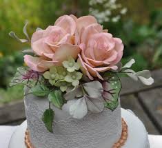 small wedding cake with roses hydrangea begonia leaves and