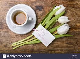 cup of coffee white tulips and card with good morning written on