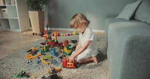 home design game videos little cute boy sitting on the floor and enjoying toys at home