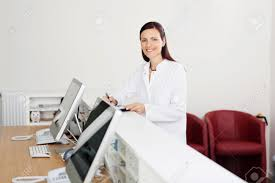 Standing Reception Desk by Smiling Female Doctor Standing At The Reception Desk Stock Photo