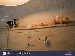 plastic farmyard animals on wooden shelf in kitchen stock photo