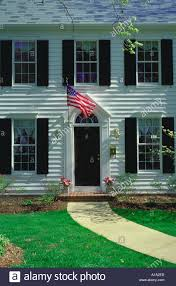 american flag hangs beside the front door of a traditional