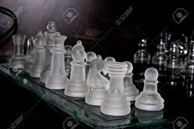 shown at an angle a frosted glass chess set on a glass chess
