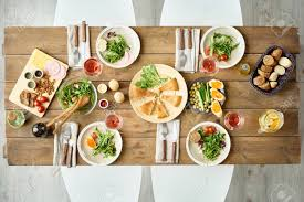 set table to dinner above view of dinner table with delicious food set for four in