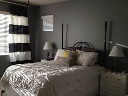adding some interesting value with gray paint bedroom in modern black metal bedstead with white bedcover also pillows beside desk lamp on nightstand in gray wall