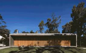 slatted timber doors unfold along house in uruguay by masa arquitectos