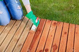 applying protective varnish on a patio wooden floor maintenance
