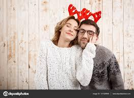 couple in fake deer horns smiling over wooden background u2014 stock