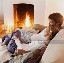 couple sitting close to each other on a sofa by a fireplace stock