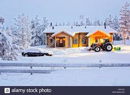 Snow At Home by Tractor Is Clearing Away Snow At The Wooden Cottage In Ruka In