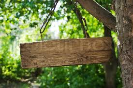 wooden sign on a chain hanging from a tree stock photo
