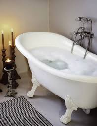 oval white bathtub with unique legs and roamntic candle in