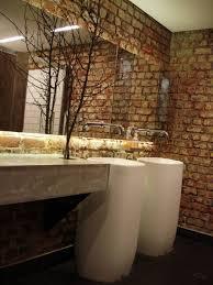 stylish bathroom vanity with large mirror and brick wall dweef