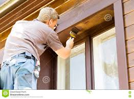 man with paintbrush painting wooden house exterior stock photo
