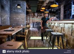 Bar Counter Entrepreneur Sitting At Bar Counter Of His Coffee Shop Stock Photo