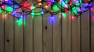 red christmas lights on wooden background with place for your text