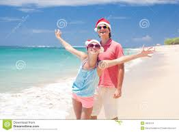 young couple in santa hats laughing on tropical beach new year
