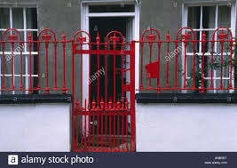 red wrought iron gate and fence in front of small victorian house