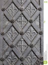 metal ornamental door with cross and fleur de lis stock photo