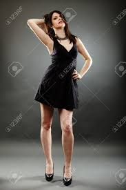 elegant young woman wearing a little black dress in glamour pose