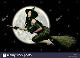 fantasy halloween witch on a broom stick flying past the moon