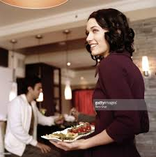 young woman serving appetizers at cocktail party stock photo