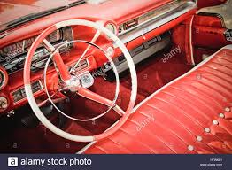 classic american car interior with red leather upholstery and