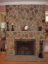 gray stone wall panel surrounding curved black iron fireplace