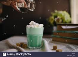 woman decorate with colored edible sparkles green mint coffee