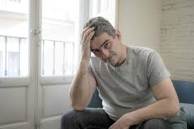 looking with grey hair sad and worried man with grey hair sitting at home couch looking