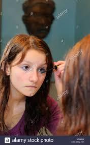 young teenage applying mascara in the bathroom mirror stock
