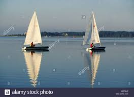two people sailing laser dinghies in the early morning calm cape