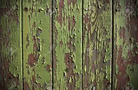 green paint peeling from a wooden panel door showing the wood