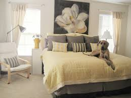 yellow bedcover also pilows beside arc floor lamp behind yellow bedcover also pilows beside arc floor lamp behind loungechair in gray bedroom paint color using white nightstand and houseplant on pot
