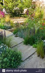 small garden with winding stone paving gravel path and seating
