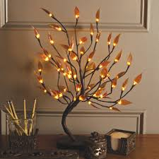 decorating brown tree with lighted branches on wooden floor and