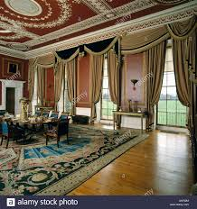 ornate ceiling and swagged curtains at tall windows in dining room
