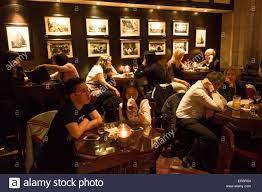 people sit at tables in cafe bar in the peace hotel on the bund in