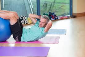 sedere di uomo uomo senior che fa sedere ups alla palestra immagine stock