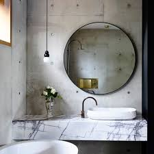 concrete marble bathroom with round mirror and side light home