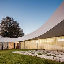 houses magazine curving roof and stone walls create seclusion for house by noarq