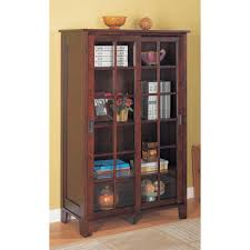 dark brown wooden bookcase with four shelves and sliding glass
