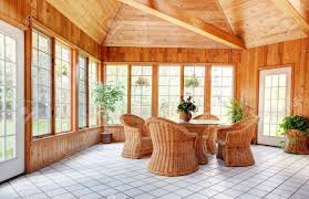 wooden wall sun room interior with natural wicker furniture